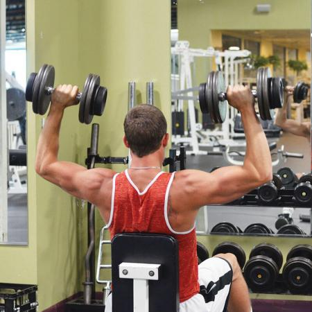 Bloomington Workout - man lifting weights in front of mirror